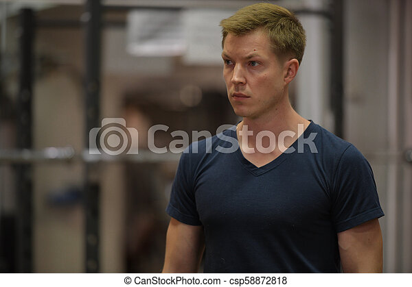 Young handsome Scandinavian man thinking at the gym - csp58872818
