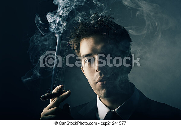 Young handsome stylish man smoking cigar - csp21241577