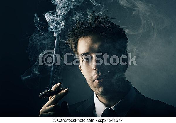 Young handsome stylish man smoking cigar - csp21241577