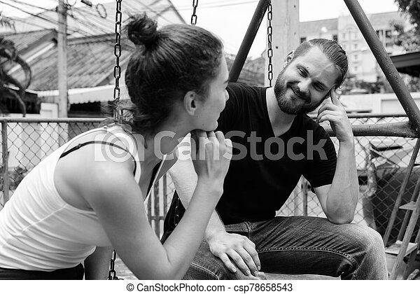 Young happy bearded man looking at young beautiful woman smiling and sitting on metal swings together in love at the old playground - csp78658543