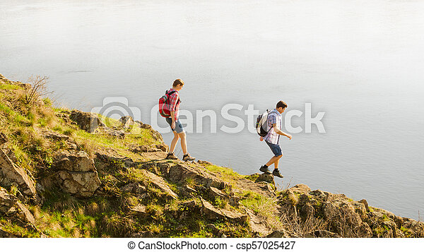 Young Happy Couple Hiking with Backpacks on the Beautiful Rocky Trail at Sunny Evening. Family Travel and Adventure. - csp57025427