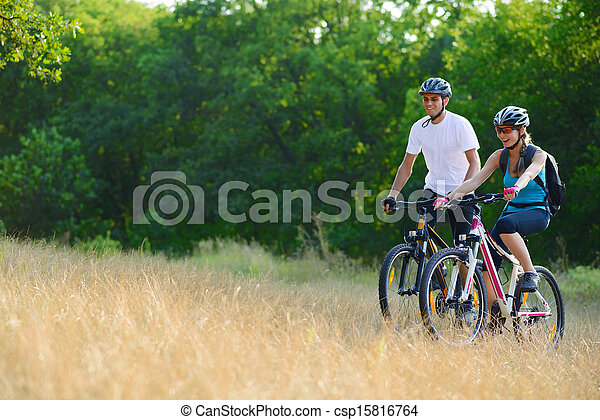 Young Happy Couple Riding Mountain Bikes Outdoor - csp15816764