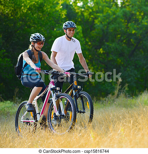 Young Happy Couple Riding Mountain Bikes Outdoor - csp15816744