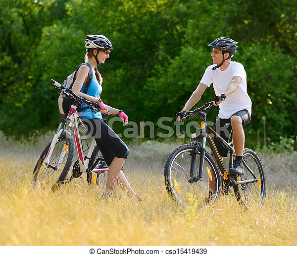 Young Happy Couple Riding Mountain Bikes Outdoor - csp15419439