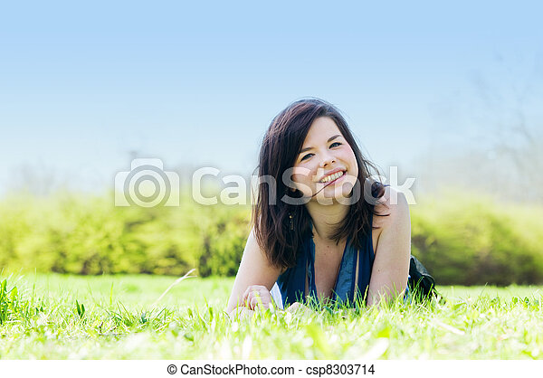 Young happy girl lying on grass - csp8303714