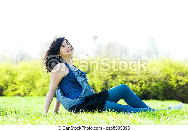 Young happy girl lying on grass - csp8303393