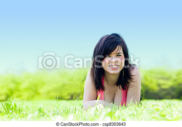 Young happy girl lying on grass - csp8303643