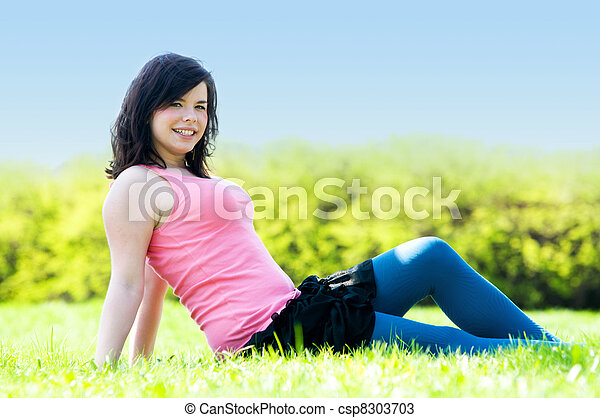 Young happy girl lying on grass - csp8303703