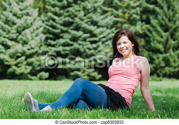 Young happy girl lying on grass - csp8303933