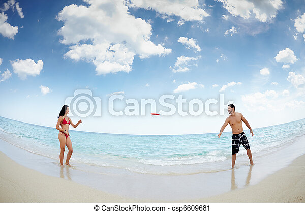 young happy man and woman playing with frisbee - csp6609681