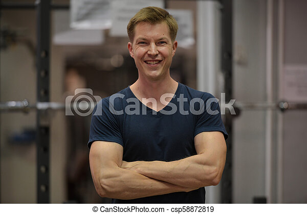 Young happy Scandinavian man with arms crossed at the gym - csp58872819