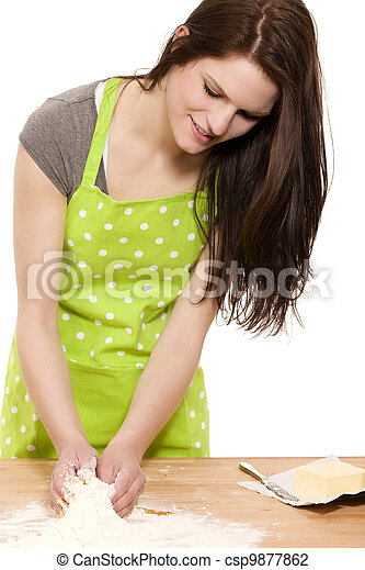 young happy woman mixing dough for baking on a table with white background - csp9877862