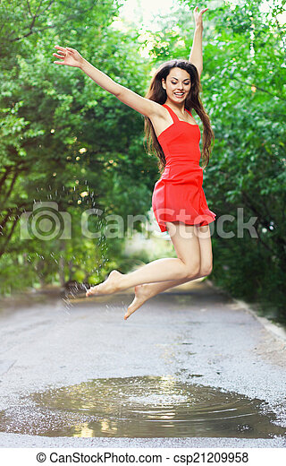Young happy woman wearing red dress jumping into a puddle - csp21209958