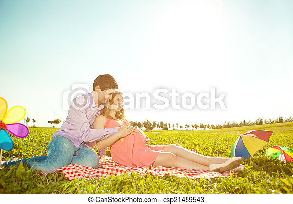 Young healthy beauty pregnant woman with her husband and balloon - csp21489543