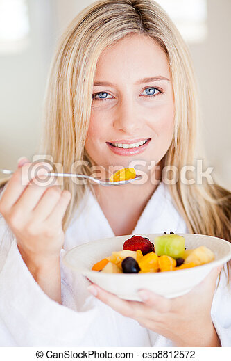 young healthy woman eating fruit salad - csp8812572
