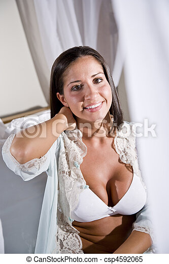 Young Hispanic woman sitting on white canopy bed - csp4592065