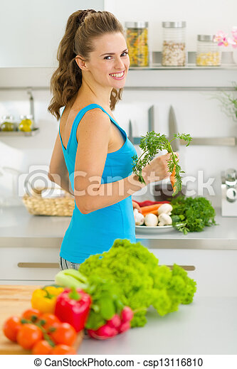Young housewife preparing vegetables in kitchen - csp13116810