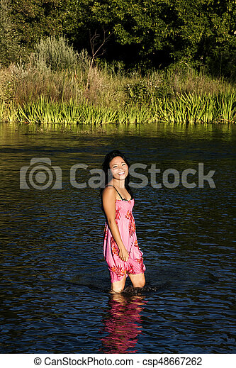 Young Japanese Woman Standing In River Smiling Wet Dress - csp48667262