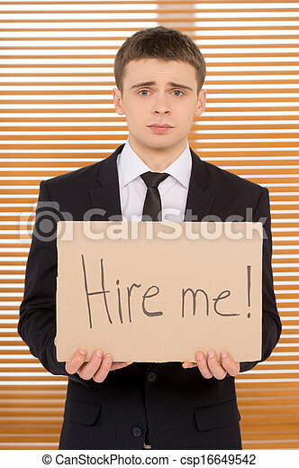 Young jobless man showing plate with sign hire me. Looking sad   - csp16649542