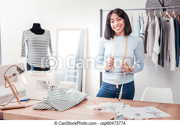Young Joyful Designer With Measuring Instrument Round Her Neck Self Employed Waist Up Of Young Joyful Designer Standing In Modern Studio While Keeping Measuring Instrument Round Her Neck And Looking