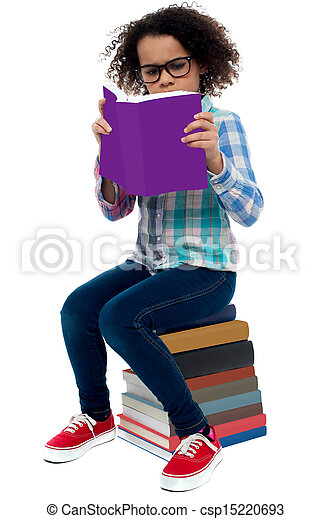 Young kid concentrating while reading a book - csp15220693