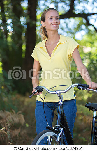 young lady standing in the forest with bicycle - csp75874951