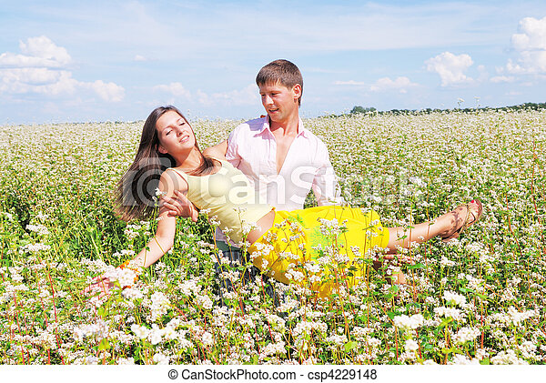 Young lovely couple playing on a flower field - csp4229148