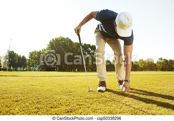 Young male golfer placing golf ball on a tee - csp50338296