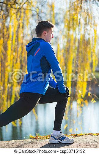 Young Male Runner Stretching in the Park in Cold Sunny Autumn Morning. Healthy Lifestyle and Sport Concept. - csp53715132