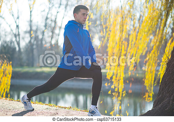 Young Male Runner Stretching in the Park in Cold Sunny Autumn Morning. Healthy Lifestyle and Sport Concept. - csp53715133
