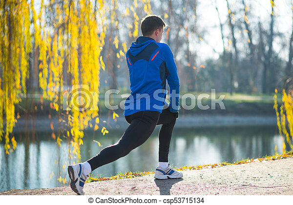 Young Male Runner Stretching in the Park in Cold Sunny Autumn Morning. Healthy Lifestyle and Sport Concept. - csp53715134