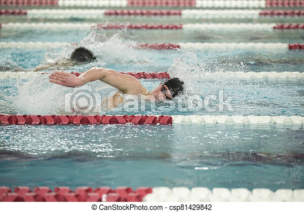 Young male swimmer swims freestyle during a competition - csp81429842