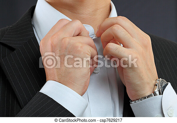 young man adjusting his suit on a black background - csp7629217