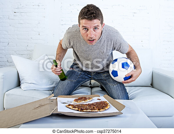 young man alone holding ball and beer bottle watching football game on television at home sofa couch - csp37275014