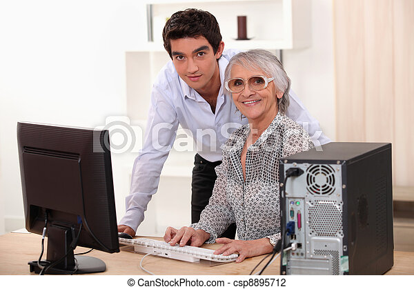 Young man and older woman using a computer - csp8895712