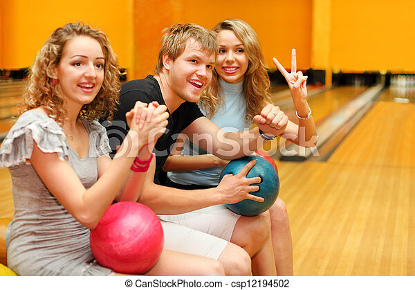 Young man and two happy beautiful girls sit, hold balls and congratulate someone in bowling club; focus on man - csp12194502