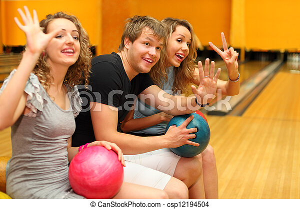 Young man and two happy beautiful girls sit, hold balls and greet someone in bowling club; focus on man - csp12194504