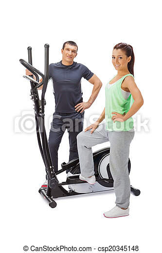 Young man and woman with elliptical cross trainer. - csp20345148