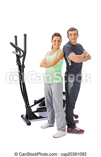 Young man and woman with elliptical cross trainer. - csp20361093