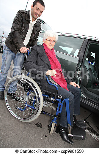 Young man assisting senior woman in wheelchair - csp9981550