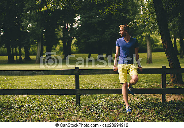 Young man by the wooden fence - csp28994912