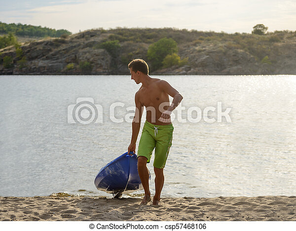 Young Man Carrying out Kayak to the Sand Beach from the Water on Beautiful River or Lake at the Evening - csp57468106