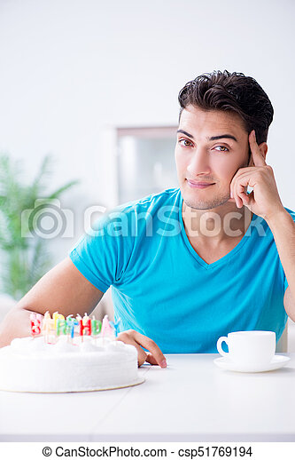 Young man celebrating birthday alone at home