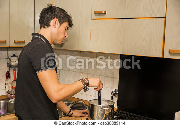 Young Man Cooking Food on Stove - csp30883114