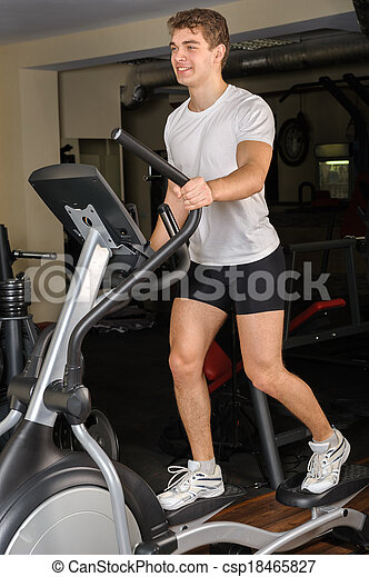 young man does workout at elliptical trainer in gym - csp18465827