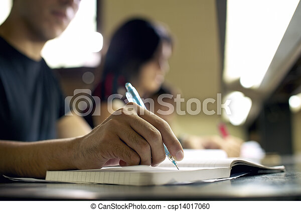young man doing homework and studying in college library - csp14017060
