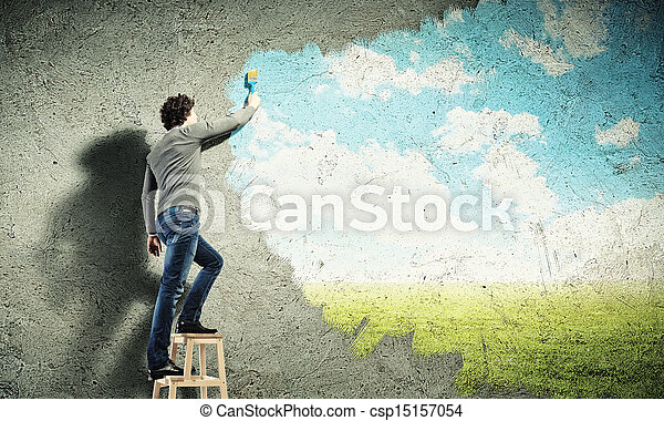 Young man drawing a cloudy blue sky - csp15157054