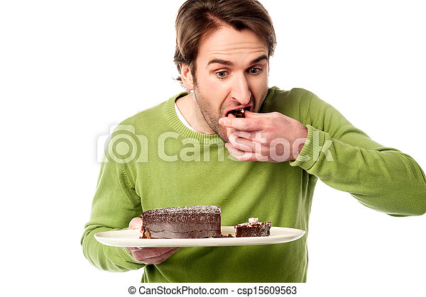 Young man eating chocolate cake - csp15609563