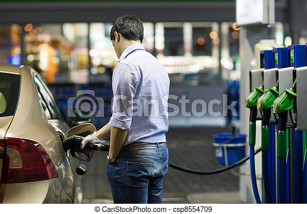 Young man fueling his car at the gas station - csp8554709