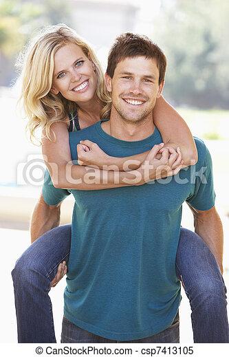 Young Man Giving Woman Piggyback Outdoors - csp7413105